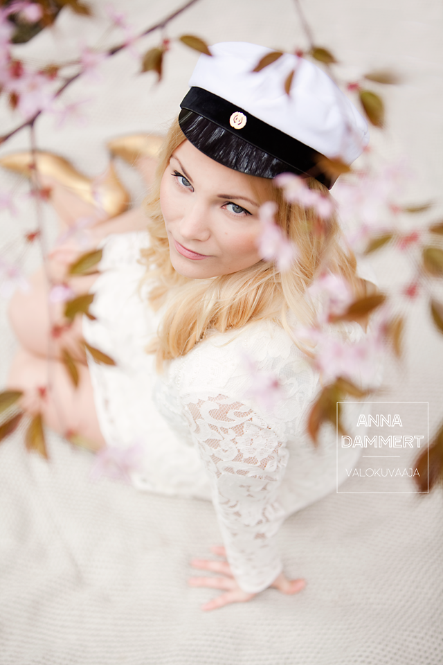 Ylioppilaskuva nuoresta naisesta kirsikankukkien kanssa