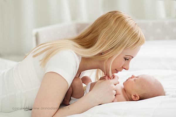 Äiti juttelee vauvalle sängyllä maaten