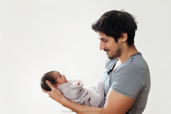Tuore isä pitelee vauvaa sylissä ja katsoo tätä