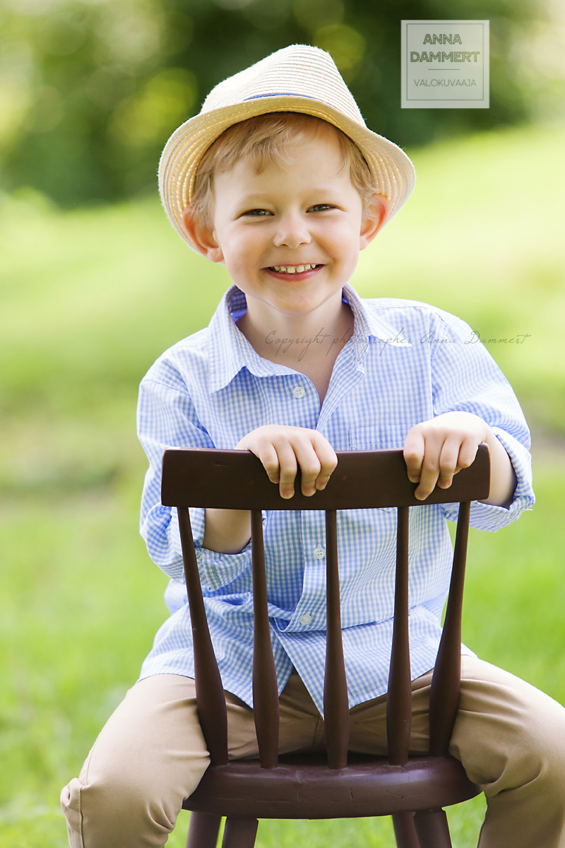 Valokuva hymyilevästä pojasta joka istuu tuolilla