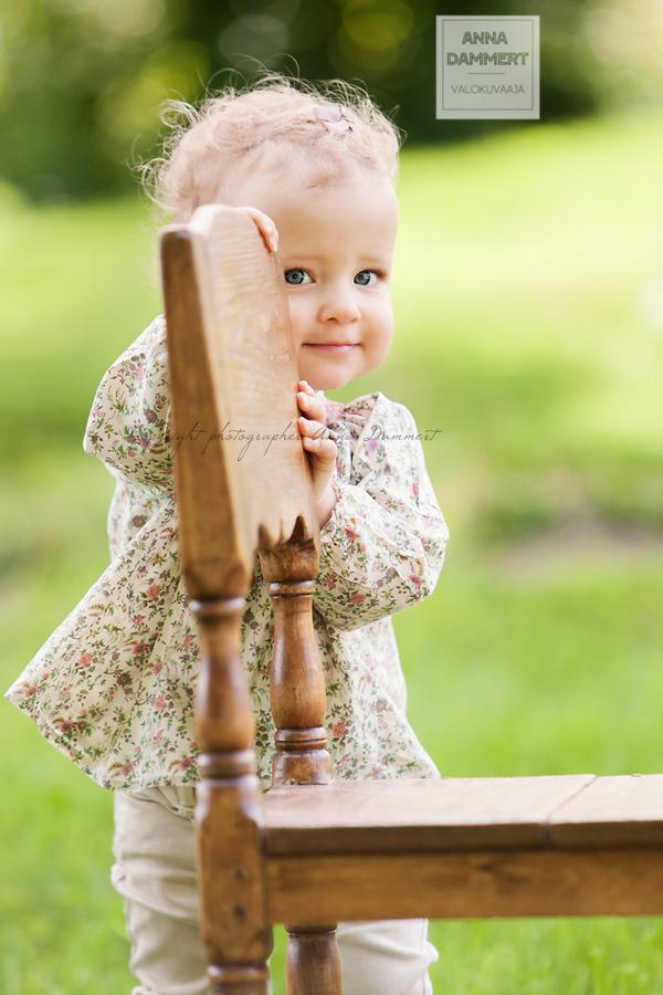 Pieni tyttö kurkistaa tuolin takaa