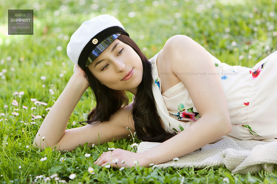 Nuori ylioppilastyttö nurmikolla kukkien keskellä