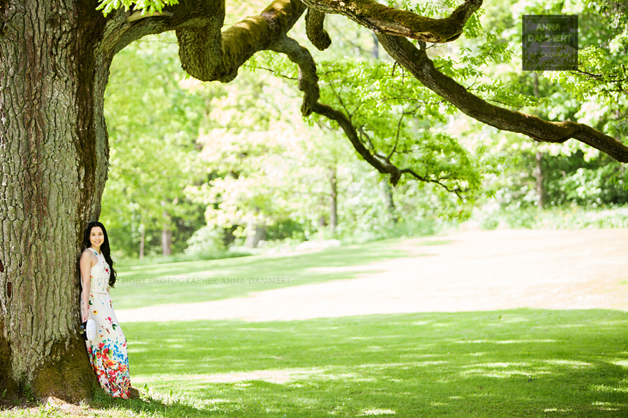 Ylioppilas vehreässä puistomaisemassa puuhun nojaamassa