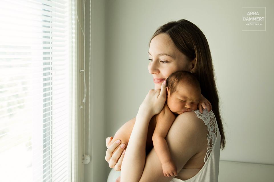 Äiti-pitää-vauvaa-olkapäällä-ikkunan-vieressä
