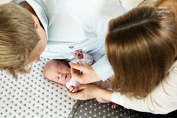 Isä ja äiti katselevat pientä vauvaa ja pitävät vauvaa kädestä kiinni